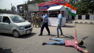 An Indian student holds Indian flag and blocks road as he shout slogans against the alleged police action on outstation students at the National Institute of Technology (NIT) Srinagar during protest demonstration in Jammu.