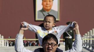 Peking'de bir çocuk babasının omuzlarının üstüne oturuyor.