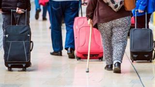 Pasajeros con sobrepeso que caminan en una aeropuerto, vistos de espaldas