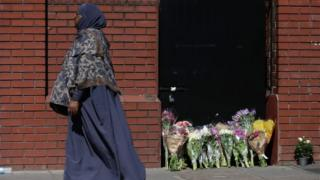 Woman passes flowers laid in Finsbury Park
