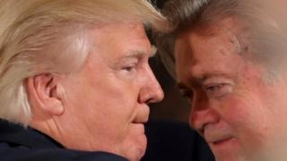 President Donald Trump talks to chief strategist Steve Bannon during a swearing in ceremony for senior staff at the White House in Washington, January 22