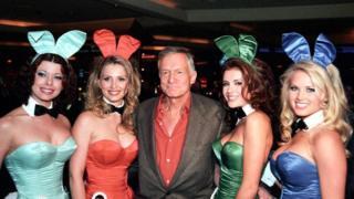 Hugh Hefner con cuatro camareras en sus uniformes de conejita Playboy.
