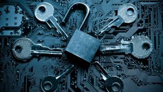 Open padlock surrounded by keys on circuit board