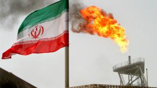 A gas flare on an oil production platform in the Soroush oil fields is seen alongside an Iranian flag in the Persian Gulf, Iran