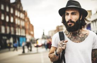 Un joven con tatuajes carga su mochila en Londres.