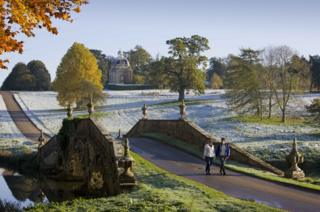 A couple walking through the wintry gardens of Stowe