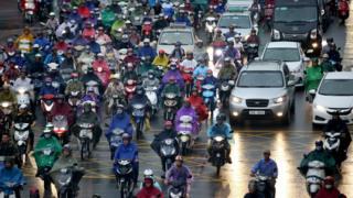 Dozens of motorbikes wait in a traffic jam in the rain in Hanoi, June 2017