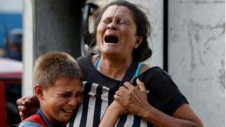 Mulher e criança chorando na porta da prisão de Valencia