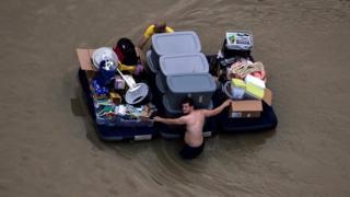 Un residente en Houston pasa por una calle inundada con sus pertenencias.