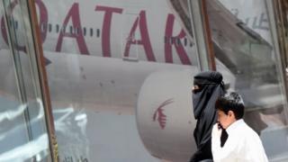 A woman and a boy walk past the Qatar Airways branch in the Saudi capital Riyadh. Photo: 5 June 2017