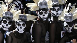 Hombres vestidos con trajes de esqueleto esperan el comienzo del desfile del Día de los Muertos en la avenida Reforma de Ciudad de México.