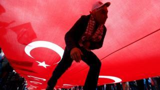 یک رای دهنده در زیر پرچم بزرگی از ترکیه