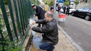 Residents of Damascus filling up water bottles in the streets during shortages