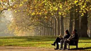 Dos personas sentadas en un banco en Hyde Park, en Londres, junto a una avenida de árboles