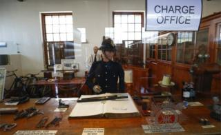 "A 1913-1957 era charge office on exhibit at the South African Police Service""s (SAPS) Heritage Services Museum in Muizenberg, Cape Town, South Africa 09 November 2017. South Africa has one of the highest violent crime rates in the world with a very high rate of murders, assaults, rapes and other crimes.The South African Police Service""s has released the crime statistics for 2017 showing as many as 2,129,001 serious crimes were recorded in 2017 an increase from 2015/16. The SAPS Heritage Services Museum dating back to before 1874 portrais various era""s of South African policing and documents famous crimes whilst also giving the visitor a view into a prison cell, courtroom and charge office"
