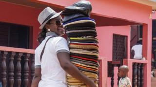A vendor sells hats and caps in Yamoussoukro on June 11, 2017. / AFP PHOTO / ISSOUF SANOGOISSOUF SANOGO/AFP/Getty Images