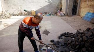 A man shovels coal he uses to heat his home in his courtyard in a village in China's Hebei province, December 5, 2017.