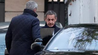 Worn French President Nicolas Sarkozy enters his vehicle as he leaves his condominium in Paris, 21 March 2018
