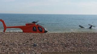 A photo shows the crashed plane and a rescue helicopter