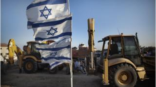 Israeli flags and construction machinery at Adom settlement (file photo)