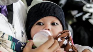 A baby drinks milk from a bottle