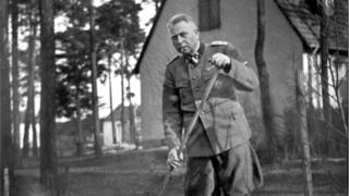 Man in Nazi uniform gardening