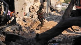 A Somali security force officer walks among ruins at scene of Saturday blast in Mogadishu