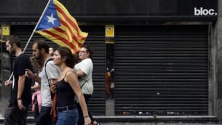 This file photo taken on 3 October 2017 shows people walking past a closed store during a general strike in Catalonia called by Catalan unions in Barcelona