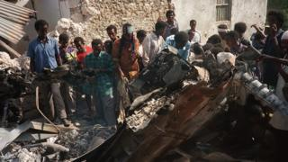 Somalis look at the wreckage of a US helicopter, in a Mogadishu street, 04 October 1993, after it was shot down.