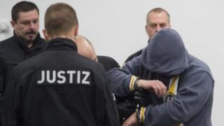 One of the suspects (right) enters the hearing room at the start of the trial in Dresden, Germany. Photo: 7 March 2017