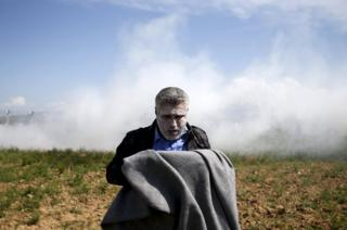 A migrant catches his breath after inhaling teargas