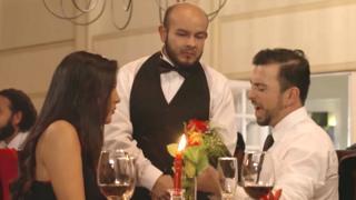 Escena de aviso en el que una pareja en un restaurante habla con el mozo.