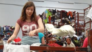 Woman sorting clothes in warehouse