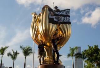 Members of political parties Demosisto, the League of Social Democrats and People Power stand on the six-meter-high Golden Bauhinia statue during a protest in Golden Bauhinia Square in Hong Kong, China, 28 June 2017