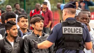 Полицейский и беженцы в лагере возле Кале