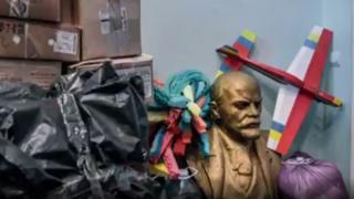 Un busto de Vladimir Lenin entre escómbros