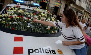 A woman displays a flower on the windshield of a vehicle of Catalan police, known as Mossos d'Esquadra during a pro-referendum rally in Barcelona on September 24, 2017.