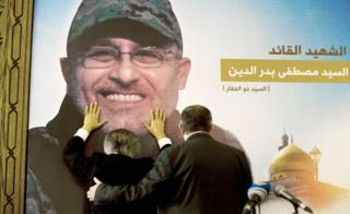 Adnan Badreddine, left, brother of top Hezbollah commander Mustafa Badreddine, grieves at his brother's picture in a southern suburb of Beirut, Lebanon, Friday, May 13, 2016.