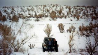 Two people stand in front of a parked car in what appears to be a snow-covered desert.