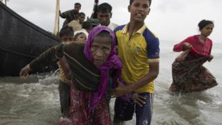 A young Rohingya man carries an elderly woman, after the wooden boat they were travelling on from Myanmar crashed into the shore and tipped everyone out in Dakhinpara, Bangladesh