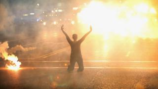 Tear gas reigns down on a woman kneeling in the street with her hands in the air after a demonstration over the killing of teenager Michael Brown by a Ferguson police officer