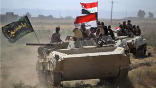 men in tank with flags