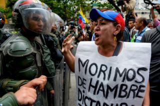 Kadın göstericinin önünde taşıdığı afişte 'Açlıktan ölüyoruz' yazıyor.
