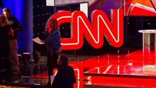 The CNN glows behind staff setting up for a Republican presidential debate in December 2015