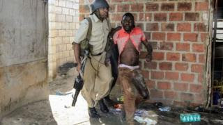 A Zambian Policeman apprehends an alleged looter in the Zingalume Compound where residents have attacked broken and looted foreign-run shops in Lusaka on April 18, 201