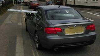 Car with guttering sticking out of window
