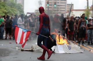 Homem vestido de super-herói carrega bandeira de Porto Rico em protesto na capital, San Juan