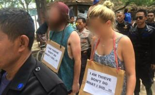 """Western man and woman being paraded by Indonesian police and security guards with a sign around their necks reading """"I am thieve [sic] don't do what I did...!!!"""""""