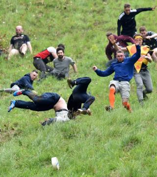 Contestants take part in the men's race at the annual cheese rolling festival on Cooper's Hill in Gloucestershire, England