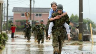 young soldier carrying older civilian in piggyback over wet ground